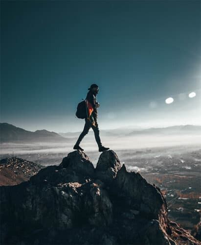 Man on a mountain top with Blue Sky Mist